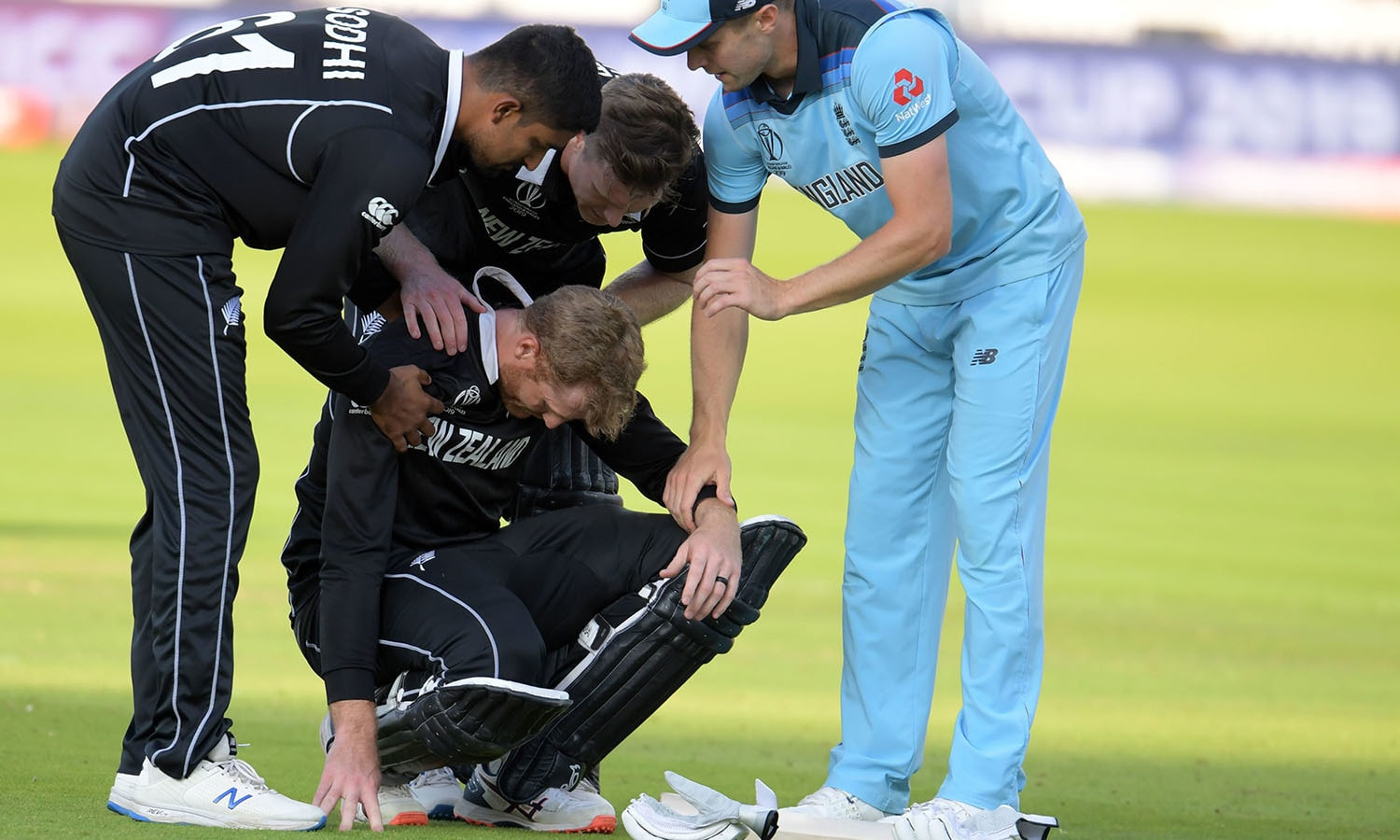 New Zealand's Martin Guptill is assisted by teammates and England's Chris Woakes after the game ended. — AFP