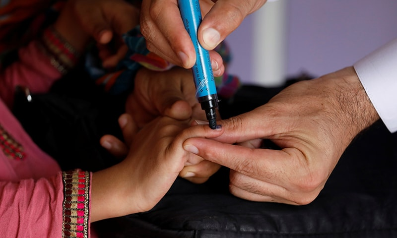 A girl gets her finger marked, after she is administered polio vaccine drops, at a civil dispensary in Peshawar on July 11. — Reuters