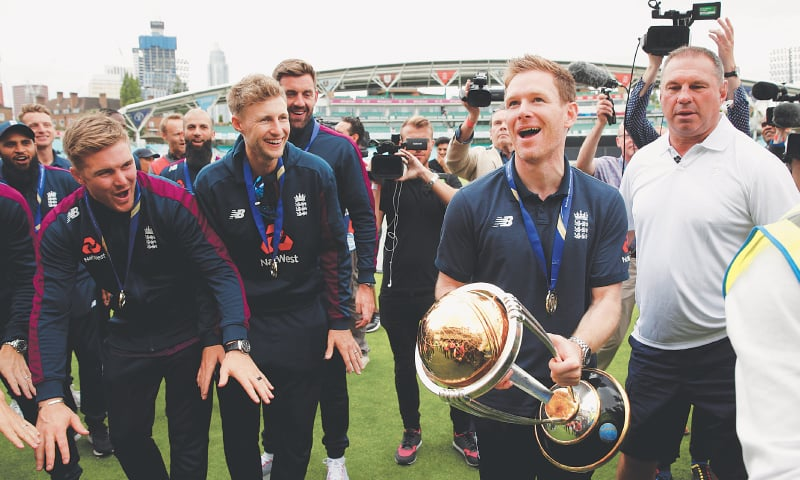 LONDON: England captain Eoin Morgan holds the World Cup trophy as team-mates look on during the celebrations at The Oval on Monday.—Reuters