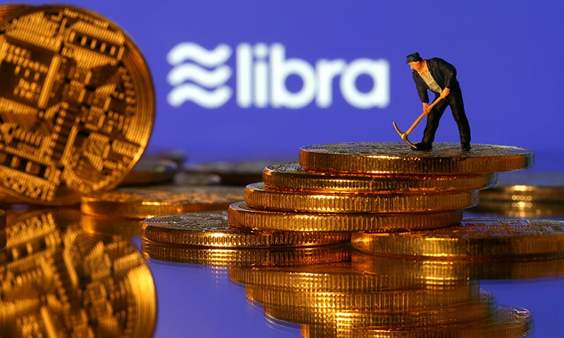 A small toy figure stands on representations of virtual currency in front of the Libra logo in this illustration picture, June 21. — Reuters