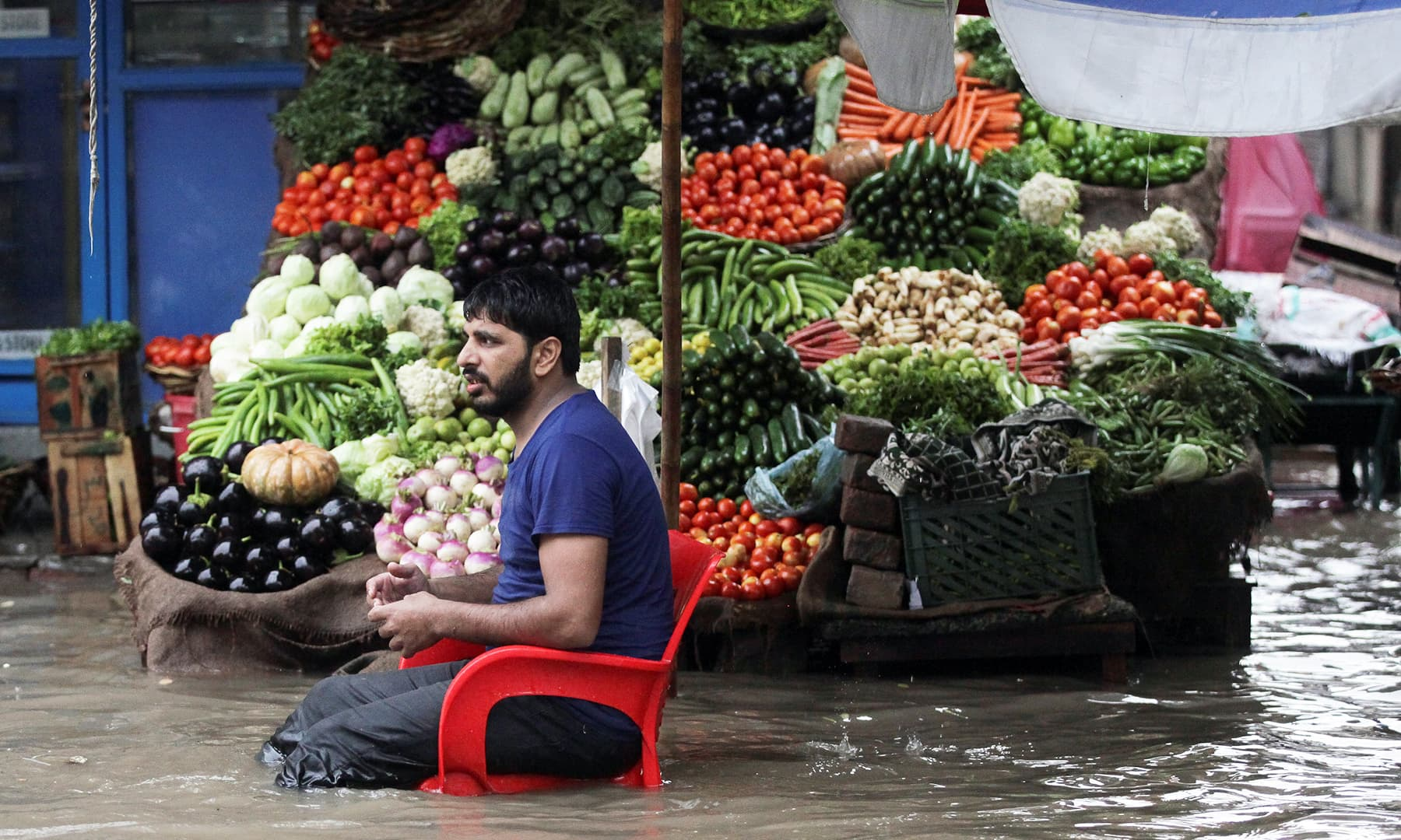 A vendor waits for customers as he sells vegetables amid floodwater, after the rain in Lahore. — Reuters