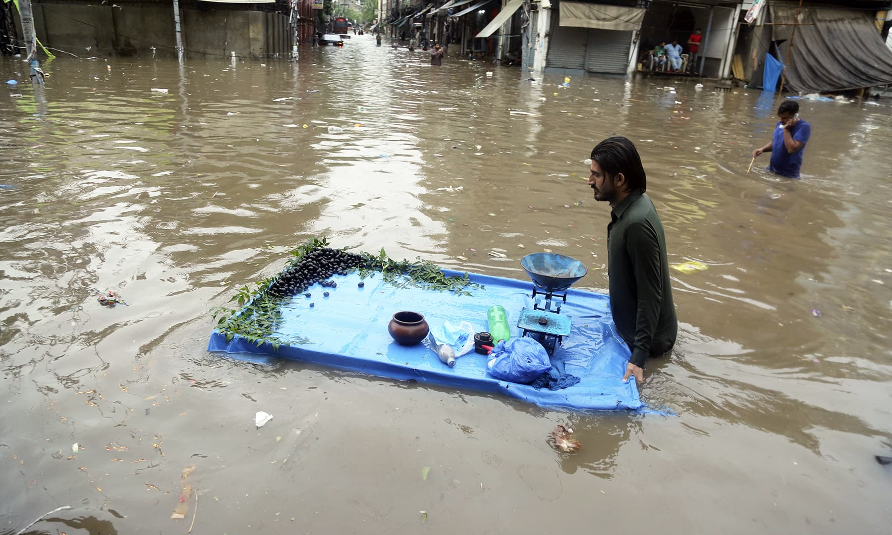 A vendor pushes his cart through a flooded street after heavy rainfall in Lahore. — Reuters