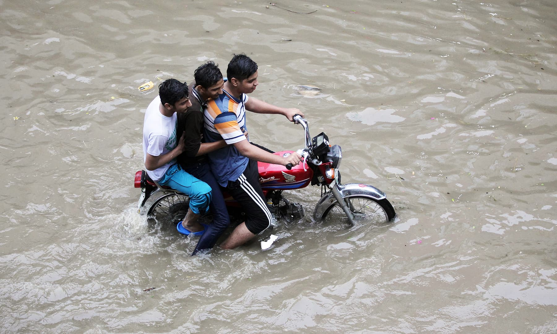 Men ride on a motorbike amid floodwater after the rain in Lahore. — Reuters
