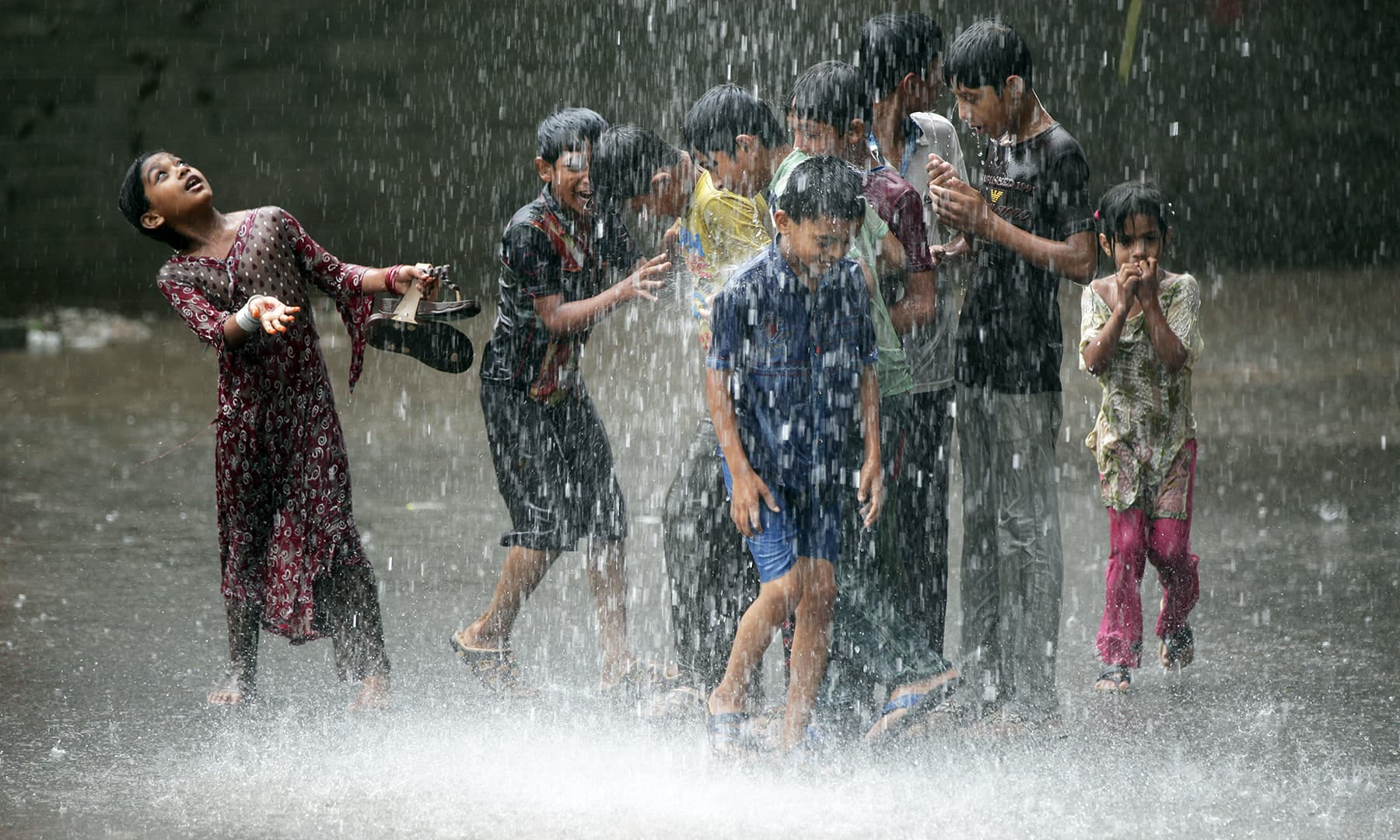Children play in the rain in Lahore. — Reuters