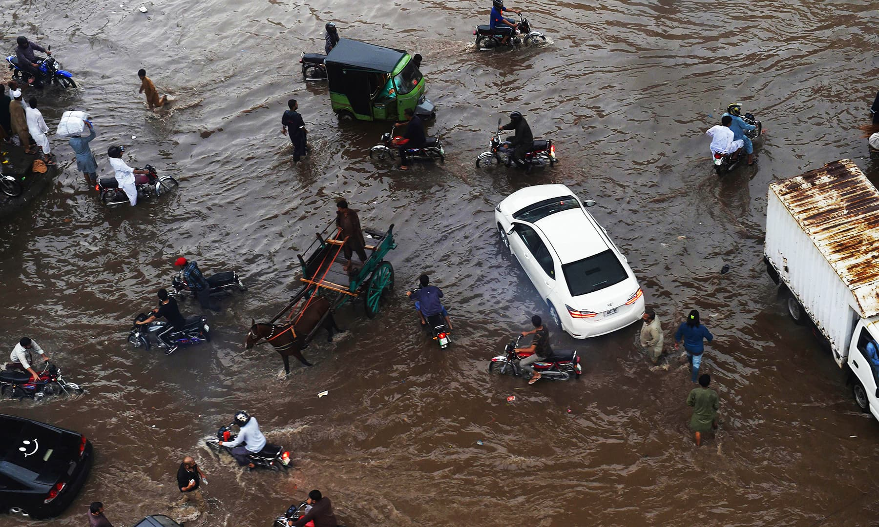 Commuters cross a flooded street after heavy monsoon rains in Lahore. — Reuters