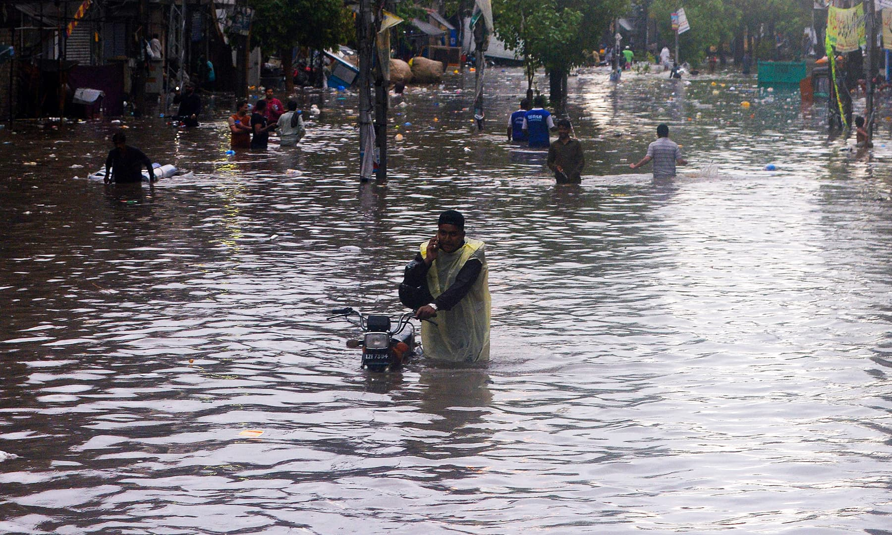 A man speaks on his phone while pushing his bike along a flooded street in Lahore. — Reuters