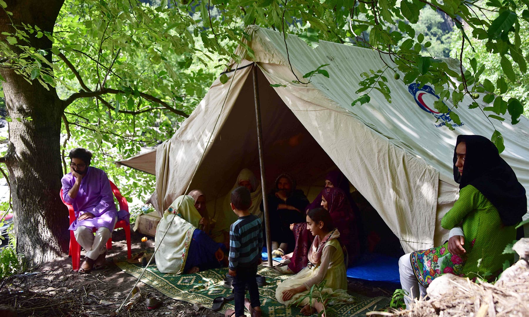 A Kashmiri family take shelter in a tent near their damaged house following heavy monsoon rains in Neelum valley. — AFP