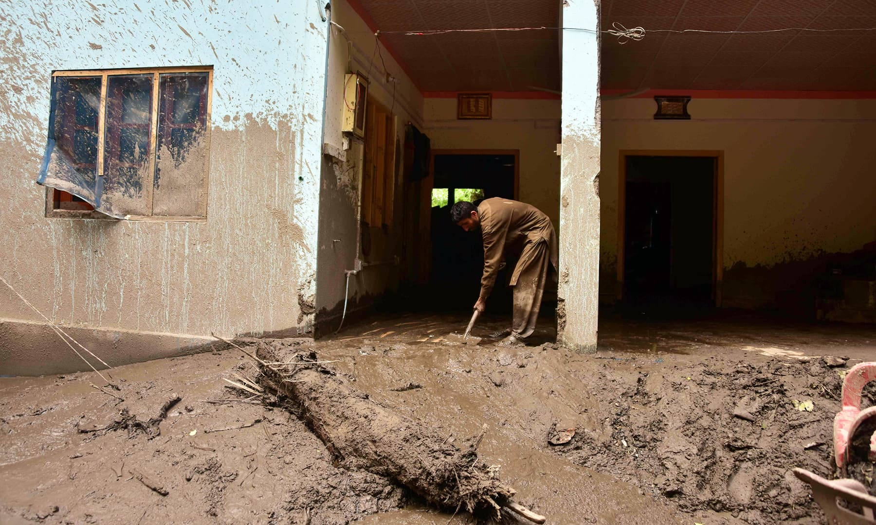 A Kashmiri removes mud from his house following heavy monsoon rains in Neelum valley. — AFP