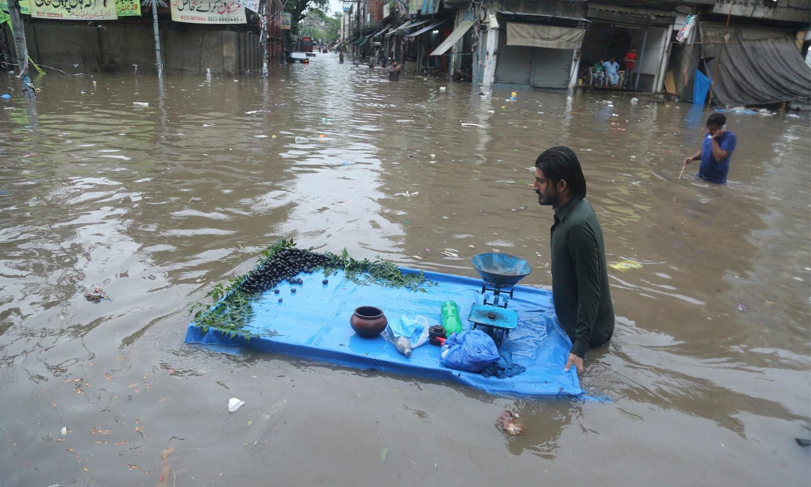 لاہور میں بارش کے بعد زیر آب سڑک پر ایک مزدور ریڑھی لے کر گھر کی جانب گامزن ہے— فوٹو: رائٹرز