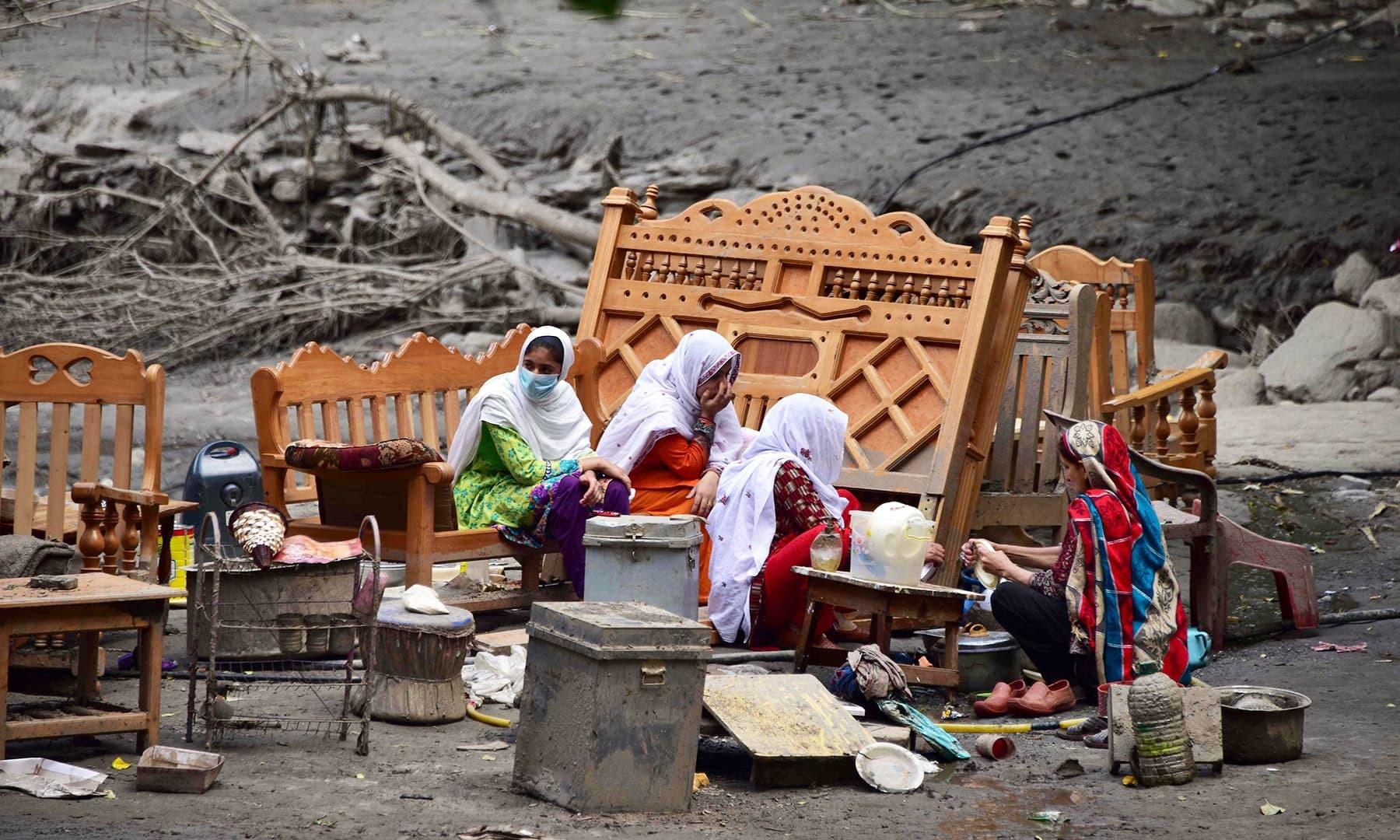 آزاد کشمیر میں نیلم کے قریب بارش کے بعد آنے والے سیلاب کے بعد گھر تباہ ہونے کے نتیجے میں ایک خاندان بے یارومددگار سڑک پر بیٹھا ہوا ہے— فوٹو: رائٹرز