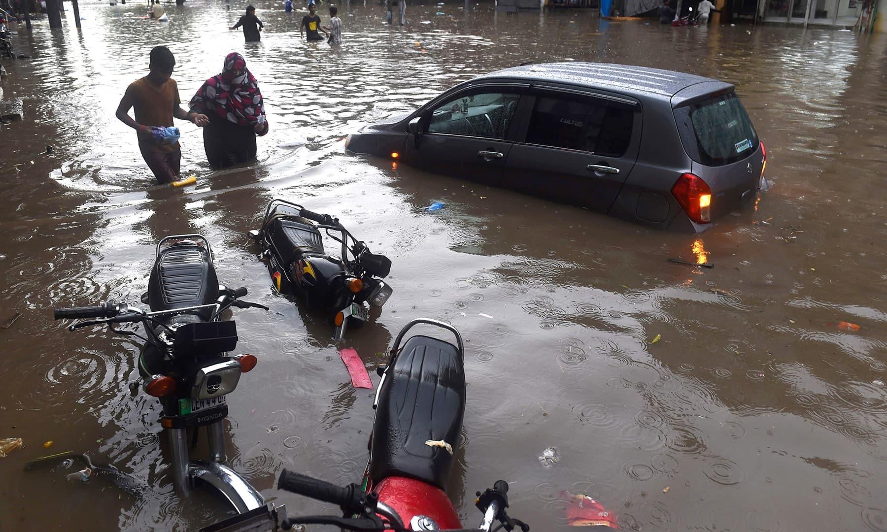 لاہور میں بارش کے بعد ایک گاڑی اور موٹر سائیکلیں آدھی سے زائد پانی میں ڈوبی ہوئی ہیں — فوٹو: رائٹرز