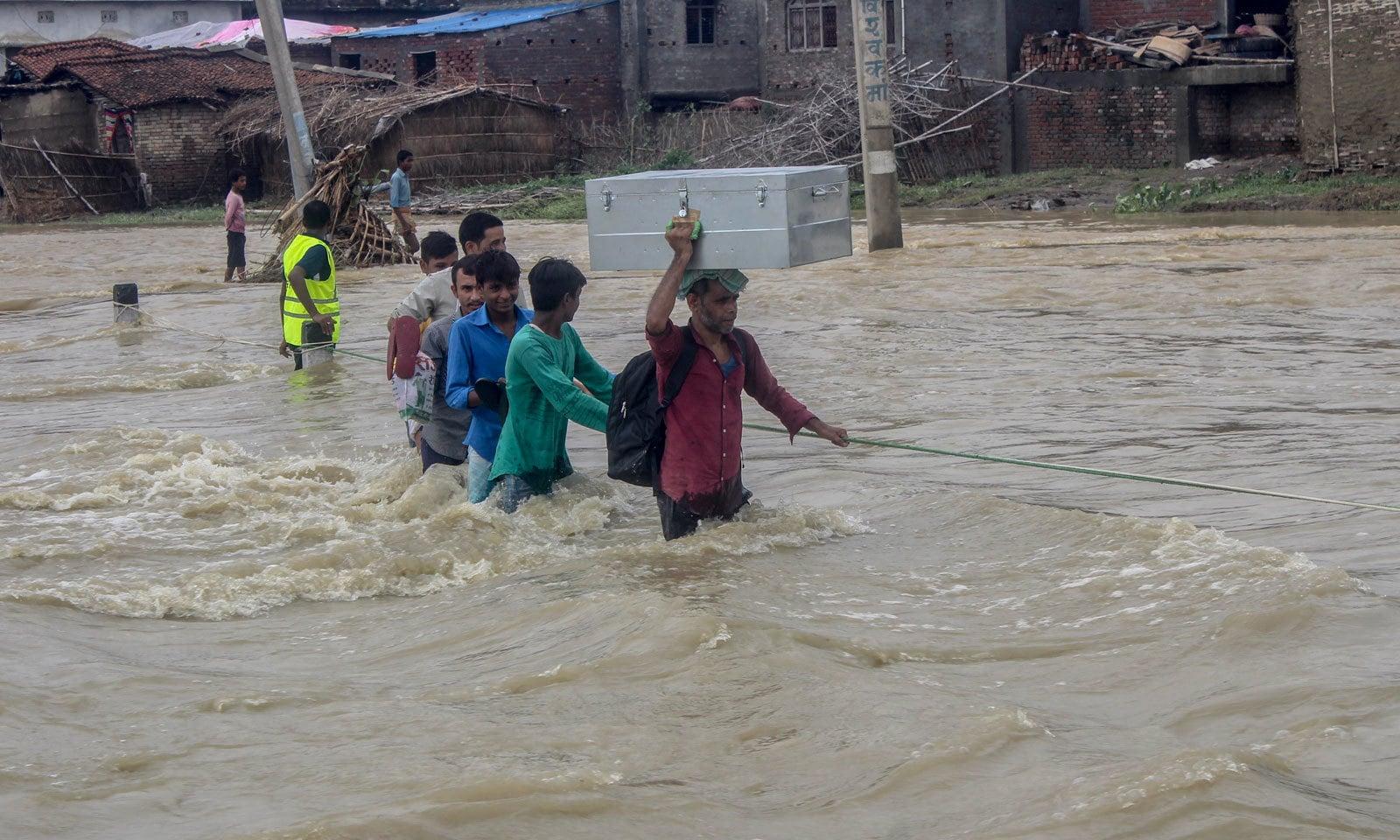 نیپال کے ضلع روتاہت میں سیلاب سے متاثرہ علاقوں کے افراد محفوظ مقامات پر نقل مکانی کر رہے ہیں— فوٹو: اے پی