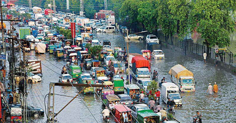A traffic mess after rainwater accumulates on Circular Road near Sheranwala Gate. — White Star / M. Arif