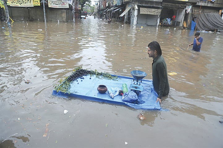 LAHORE: A vendor pushes his cart through a flooded street on Tuesday. One person was killed and at least 10 people suffered injuries in roof collapse incidents in various parts of Punjab. Persistent torrential rain badly disrupted life in Lahore, turning streets into rivulets, causing traffic jams and upsetting power supply on a large scale. — AP