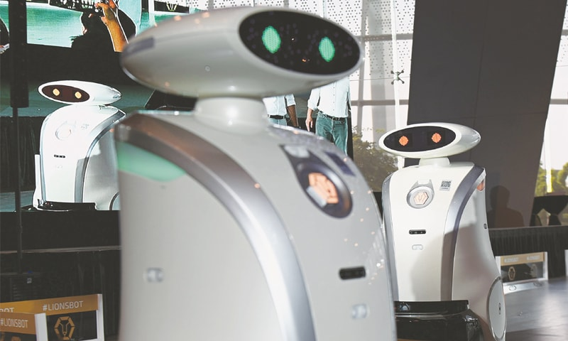 AUTONOMOUS cleaning robots moving on a platform during a recent launch ceremony in Singapore. — AFP