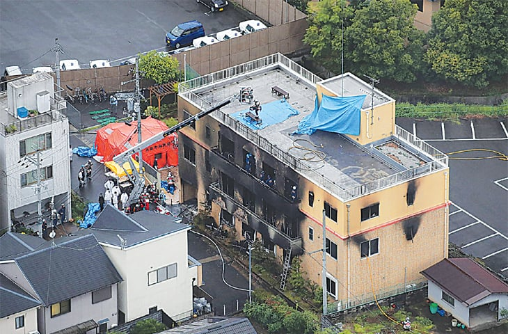 KYOTO: A rescue operation is under way at the building that was gutted after a suspected arson attack on Thursday.—AFP