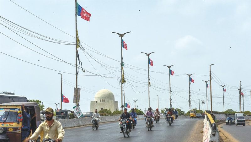 PSP flags flutter atop light poles on New M.A. Jinnah Road on Friday, near the venue of the rally.—Fahim Siddiqi / White Star