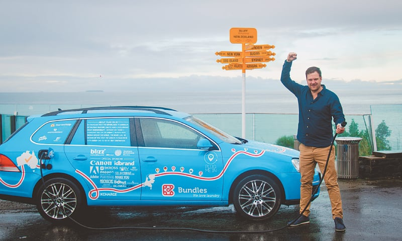 Dutchman Wiebe Wakker holds a charging cable as he poses with his electric vehicle,  the Blue Bandit, after travelling through 34 countries to reach Bluff, New Zealand's most southern tip.—Reuters