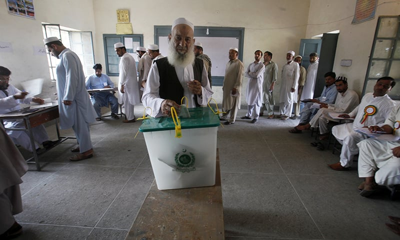 A tribesman casts his vote while others wait for their turn during an election for provincial seats in Jamrud. — AP