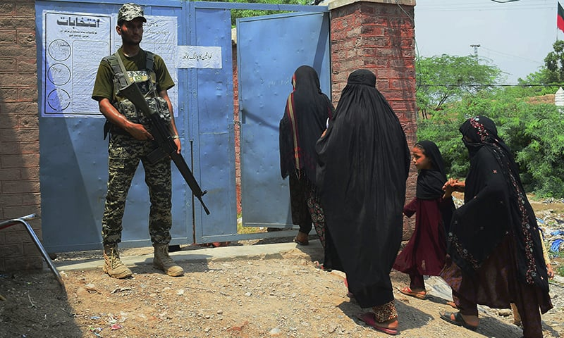 A paramilitary soldier stands guard while tribal women enter a polling station to vote during an election for provincial seats in Jamrud, a town of Khyber district, on Saturday. — AP