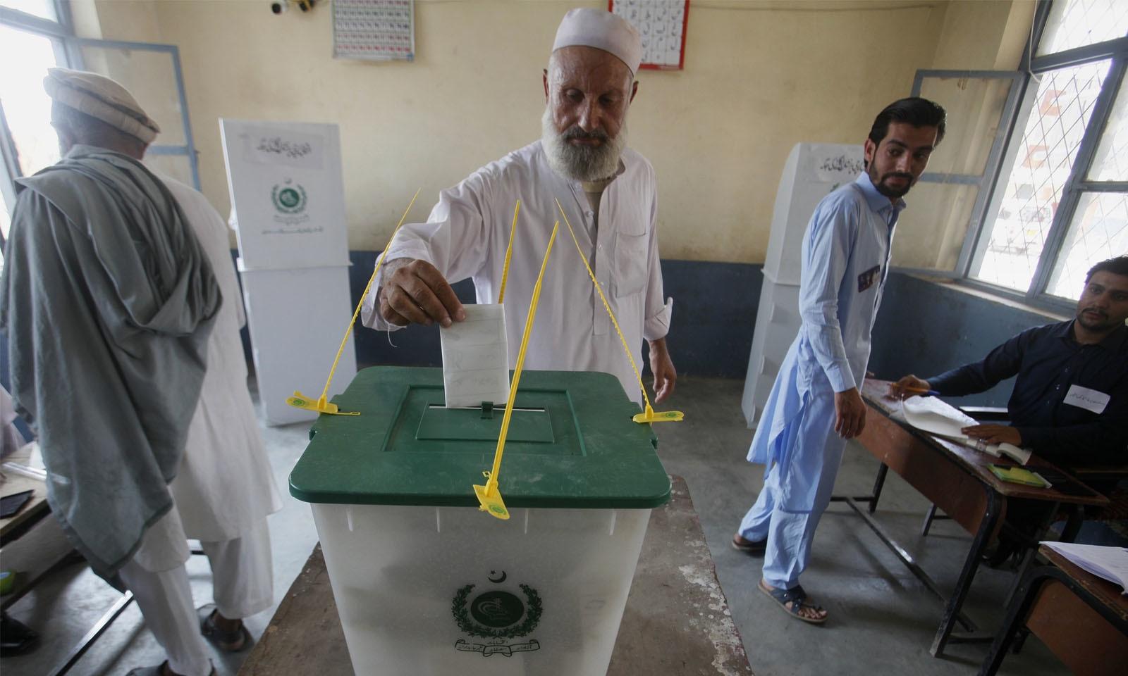 ضلع خیبر کے پولنگ اسٹیشن میں ایک بزرگ شہری اپنا ووٹ کاسٹ کررہے ہیں—فوٹو: اے پی