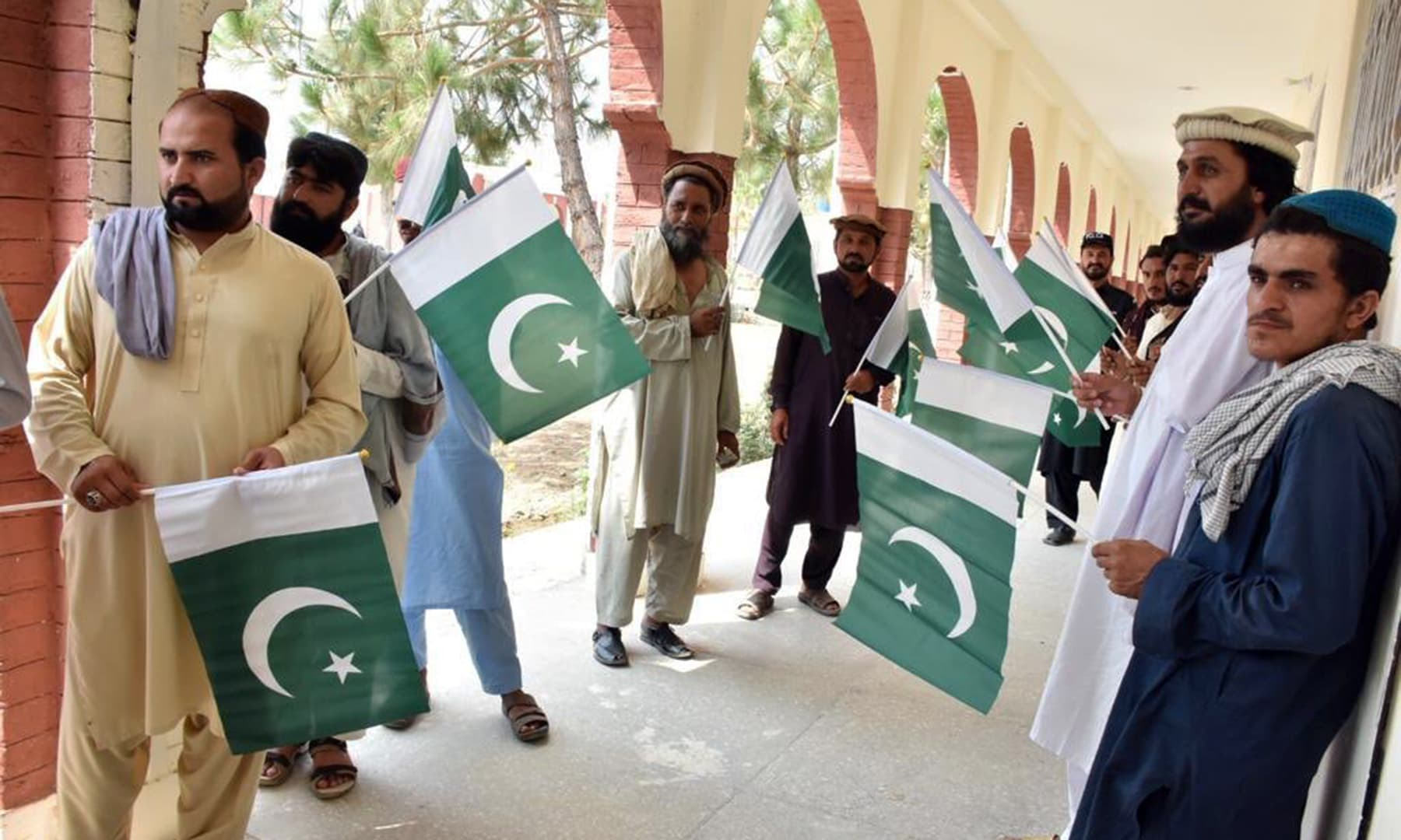 Voters are seen displaying the Pakistani flag as they gather to vote. — PTI official Twitter account