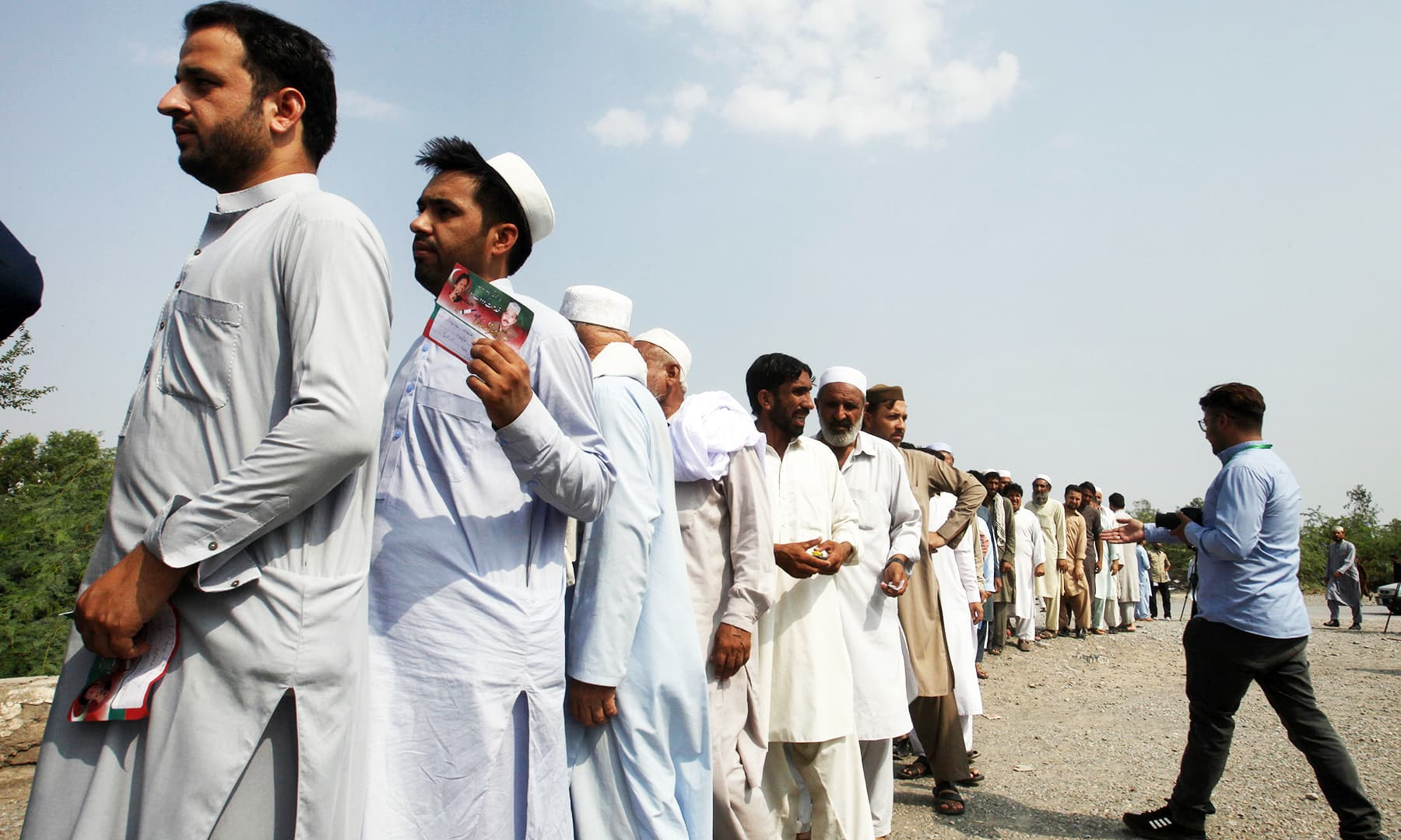 Tribesmen wait their turn to cast their vote at outside a polling station in Jamrud. — AP
