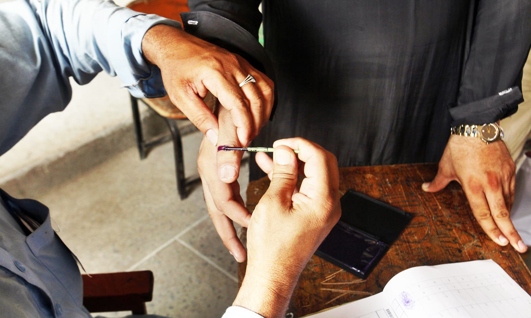 An election worker marks the thumb of voter in a polling station during an election for provincial seats in Jamrud. — AP