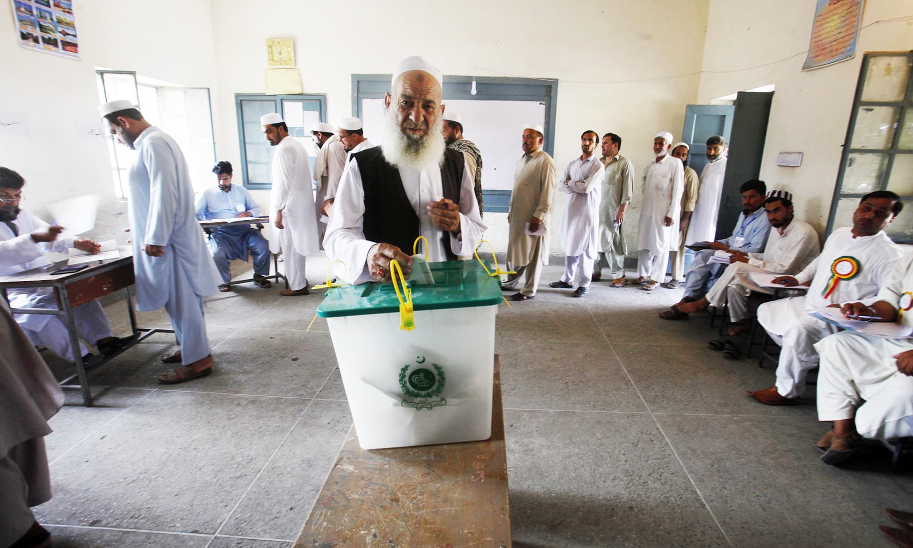 An elderly voter casts his ballot as others wait their turn at a polling station in Jamrud. — AP