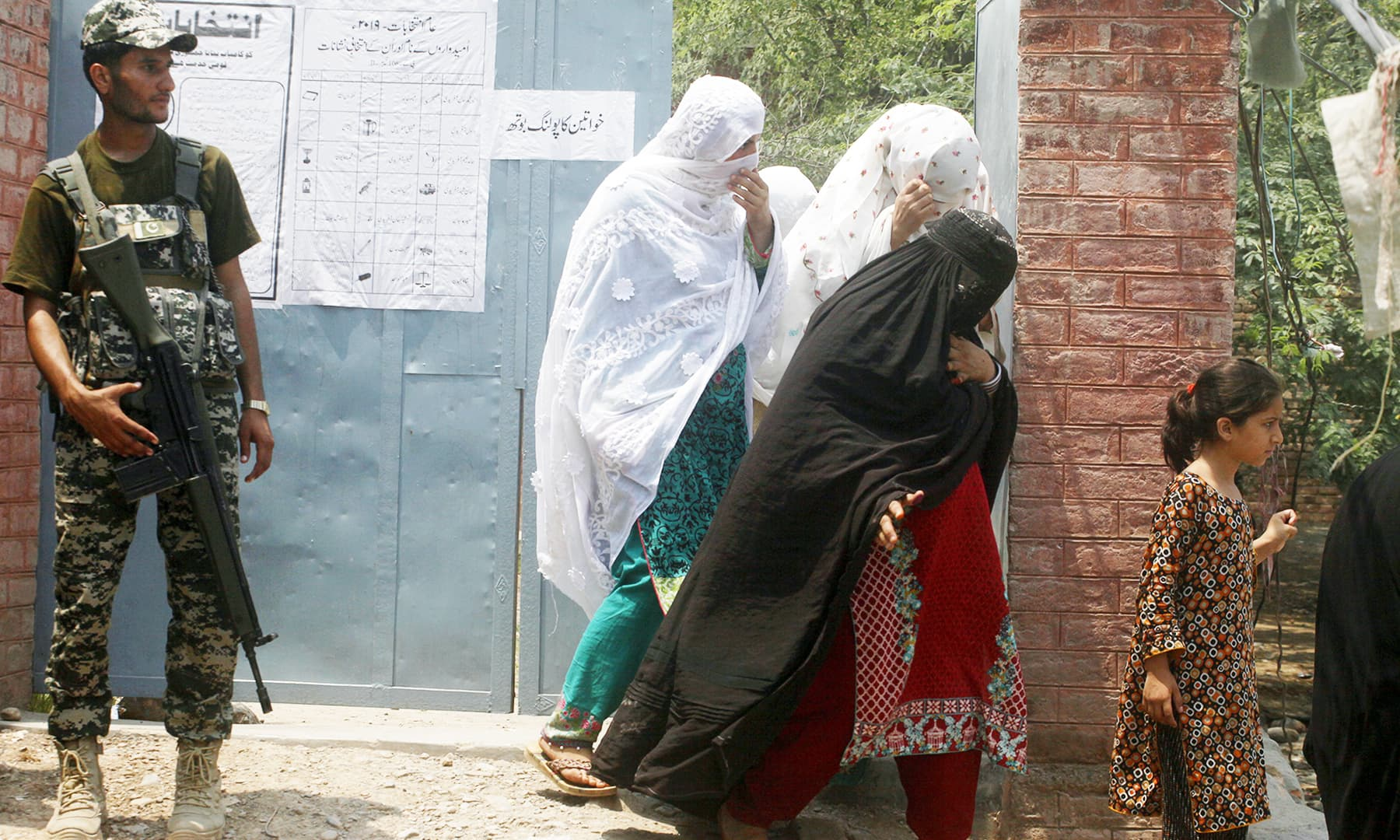 A paramilitary soldier stands guard while tribal women leave a polling station after voting in Jamrud. — AP