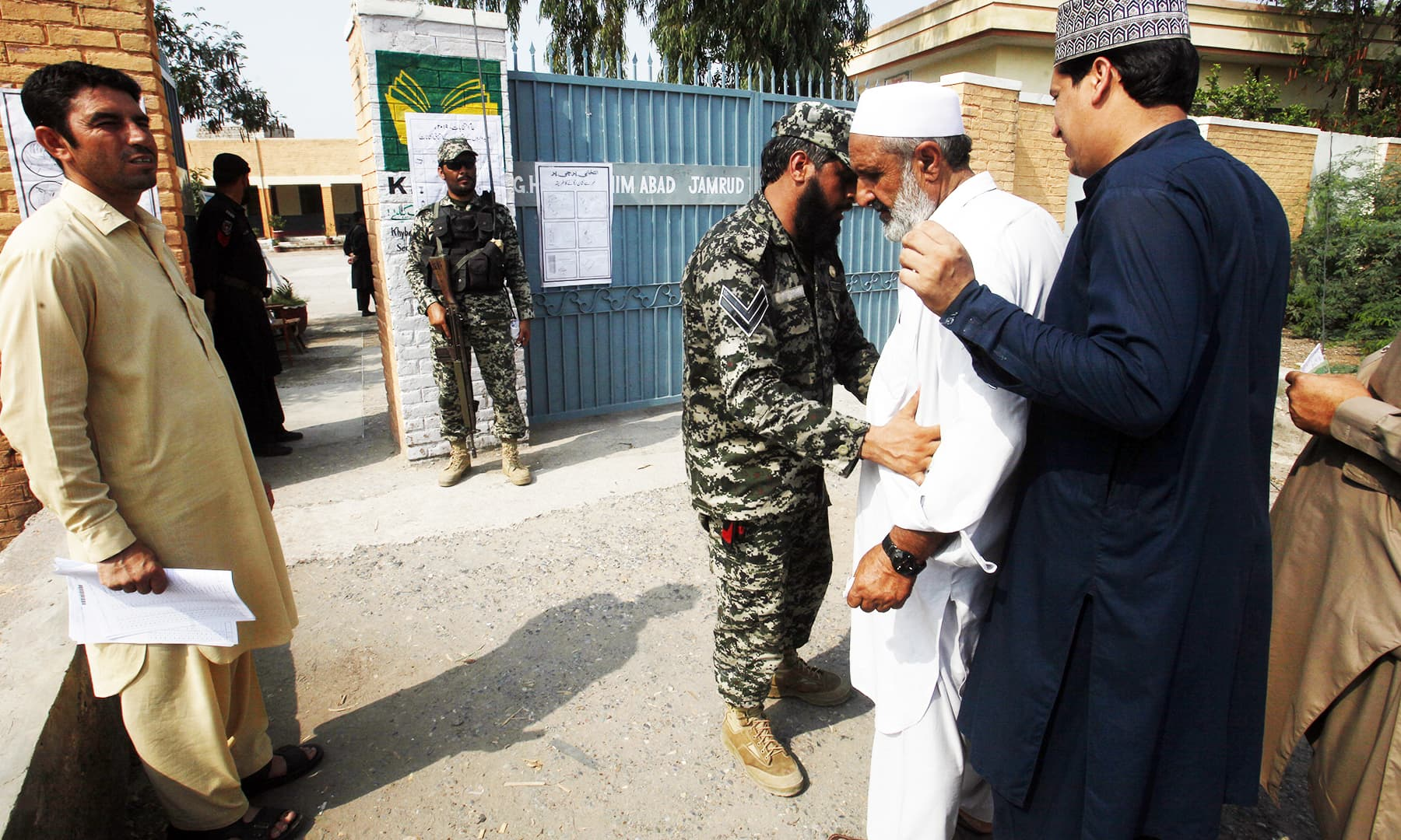 Paramilitary soldiers stand guard while another frisks a tribesman arriving to cast his vote at outside a polling station in Jamrud. — AP