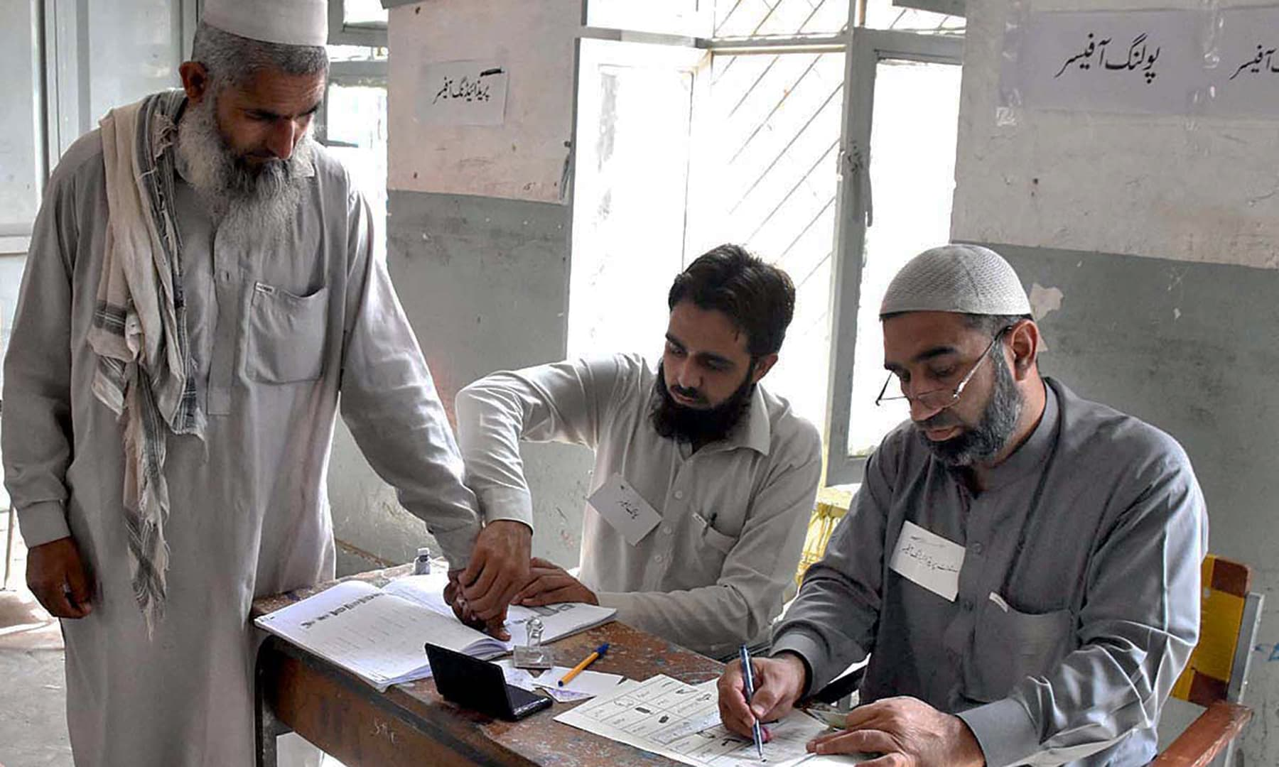 An elderly man getting a ballot paper at a polling station for PK-107 during the first Provincial Assembly election in the merged districts in Khyber area. — APP