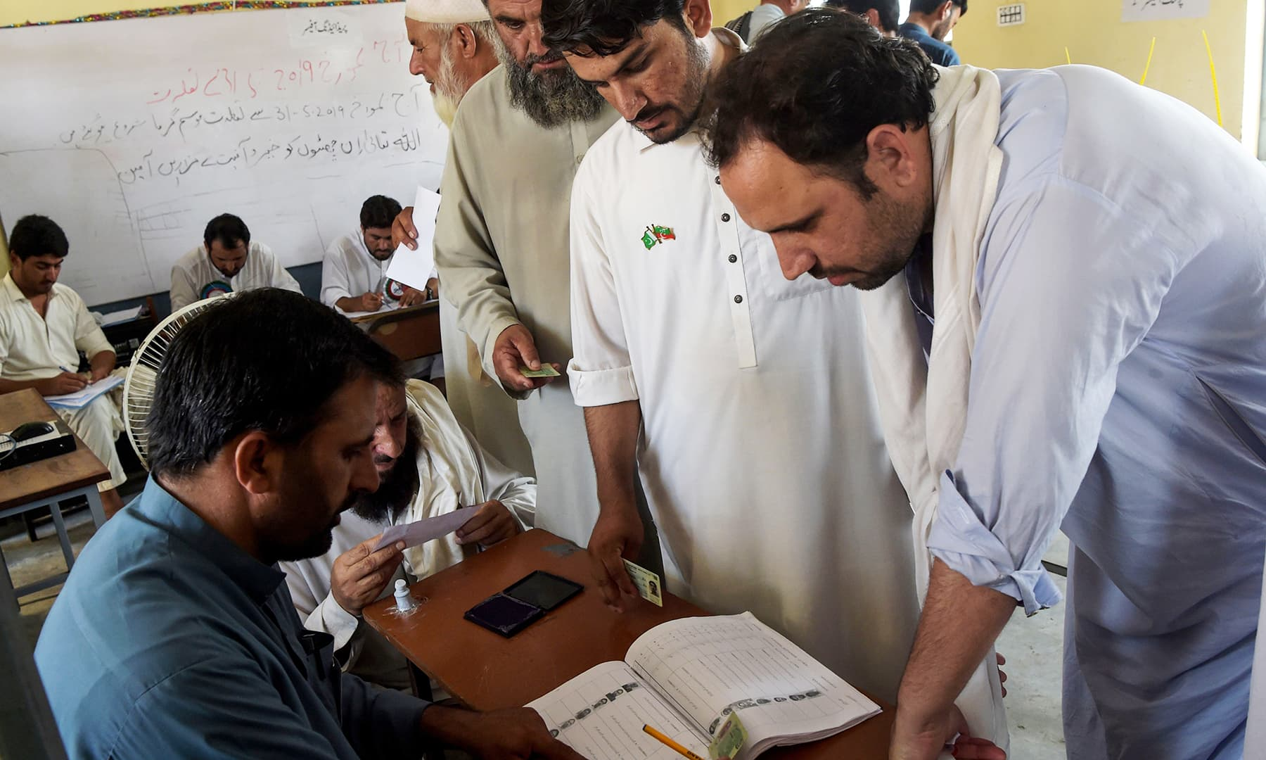 Tribesmen interact with an election official in a polling station for the first provincial elections in Jamrud. — AFP