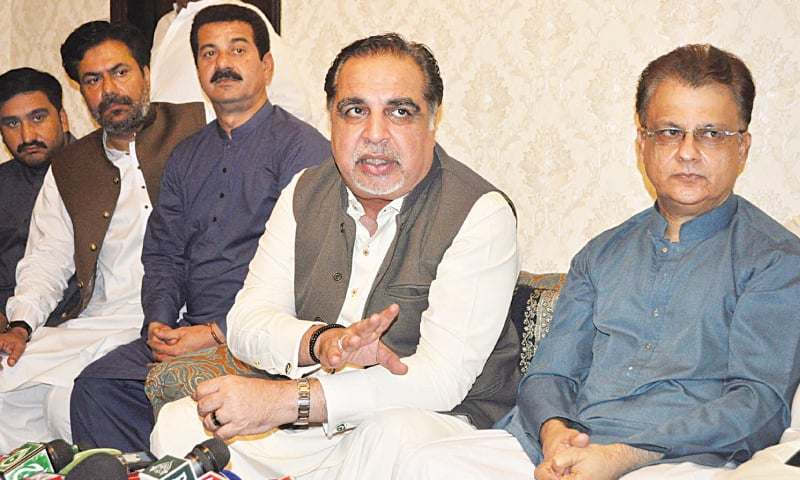 GOVERNOR Imran Ismail speaks to the media at the residence of Ayaz Latif Palijo (extreme right) in Hyderabad on Saturday.—Dawn