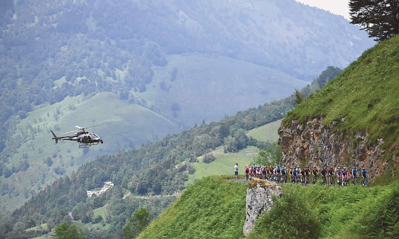 A HELICOPTER flies as cyclists ride up during the 14th stage of the Tour de France, between Tarbes and Tourmalet Bareges, on Saturday.—AFP