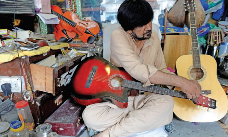 Craftsman Zain Ali adjusts the strings of a guitar.