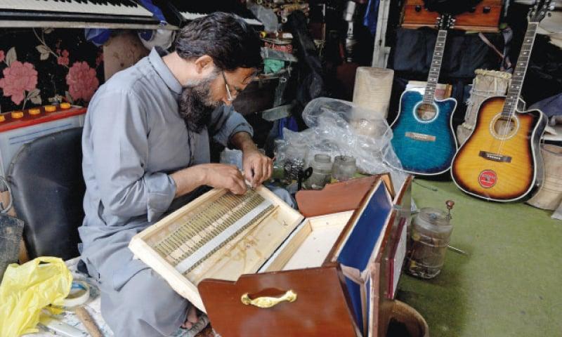 A shop worker prepares a harmonium.