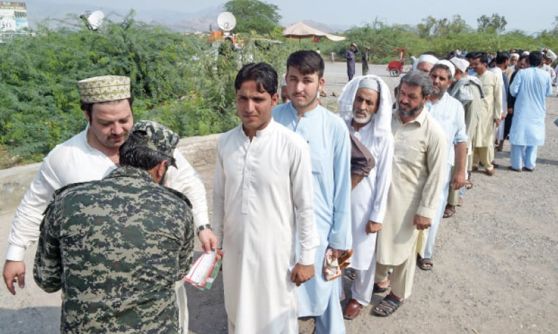 A security official frisks voters queued up outside a polling station in PK-106 constituency of Khyber tribal district on Saturday. — Photo by Abdul Majeed Goraya