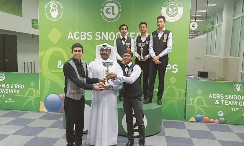 Babar Masih (L) and Zulfiqar A. Qadir receive the winning trophy from an ACBS official with the runners-up Indian team looking on after the Asian Team Championship final in Doha