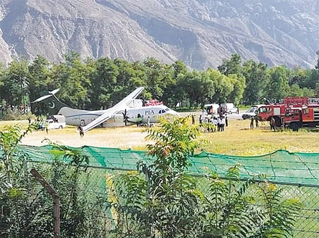 PASSENGERS and Civil Aviation Authority staff gather near the PIA aircraft after it skidded off the runway while landing at Gilgit airport on Saturday.—Dawn