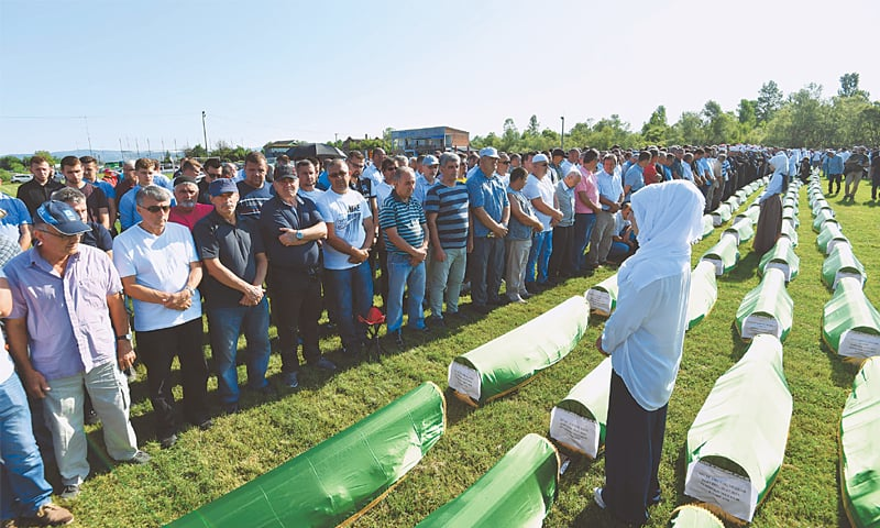 Survivors of massacre in Western-Bosnian town of Prijedor in 1992 pray near body caskets of their relatives as they prepare for burial on Saturday. — AFP