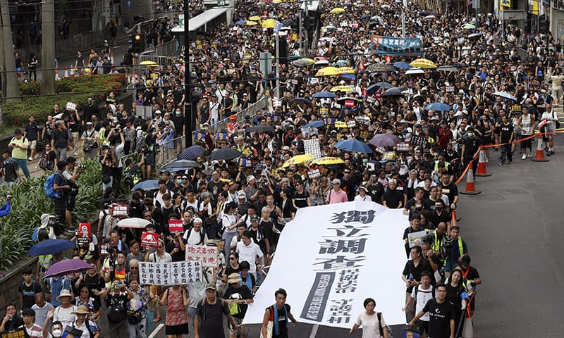 "Protesters hold a white banner reads ""Form an independent investigation on legislative committee"" during a march in Hong Kong on Sunday, July 21. — AP"