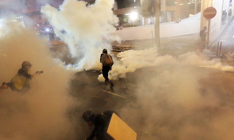 Protesters run from tear gas fired by police. — AFP