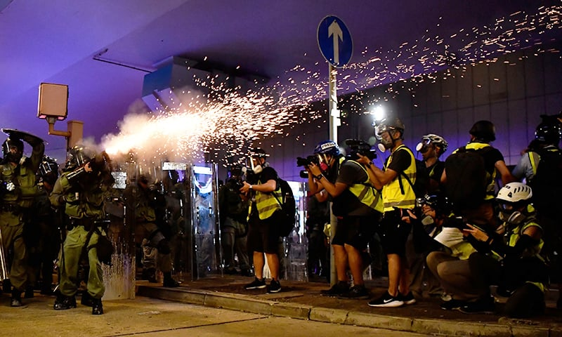 A policeman fires tear gas to disperse protesters after a march against a controversial extradition bill in Hong Kong on July 21. — AFP
