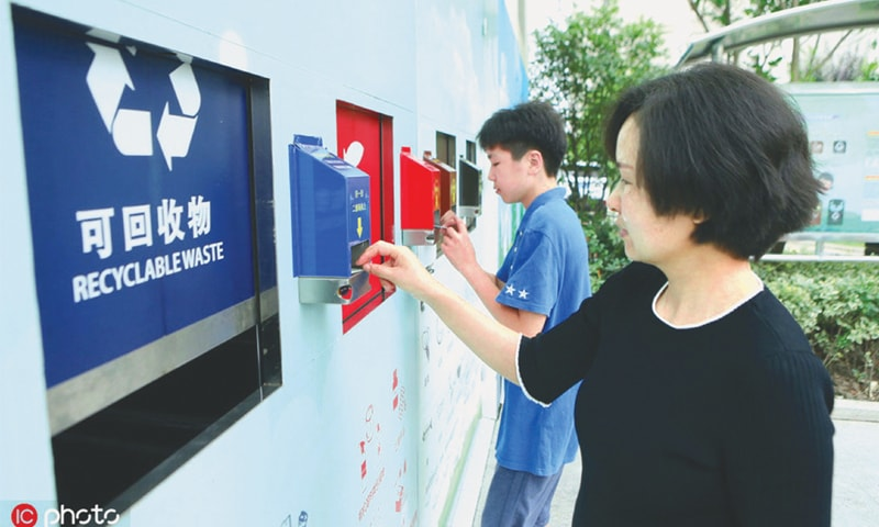 Local residents use QR code cards to open different bins for their garbage at a waste collection point in Shanghai.—ANN