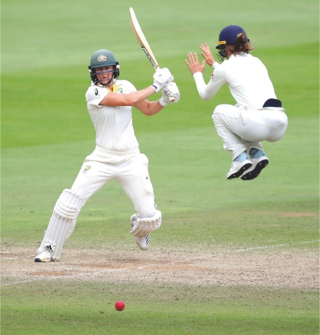 TAUNTON: Australia's Ellyse Perry drives as England's Amy Jones takes an evasive action during the Women's Ashes Test at the Coopers Associates County Ground.—Reuters