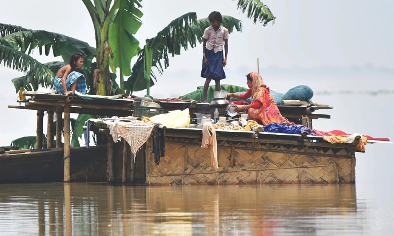 THIS photo taken on July 16 shows a family stranded atop their house in the Indian state of Assam.—AFP