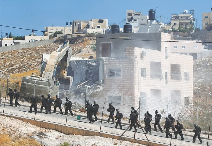 JERUSALEM: Israeli security personnel patrol an area in Sur Baher as a machine demolishes a Palestinian building on Monday.—Reuters