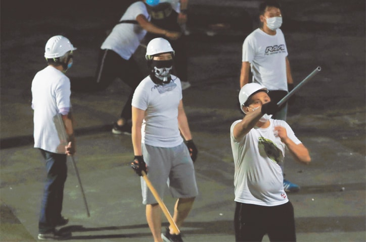 Hong Kong: Men in white T-shirts carrying poles are seen after attacking anti-extradition bill demonstrators at a train station on Monday.—Reuters