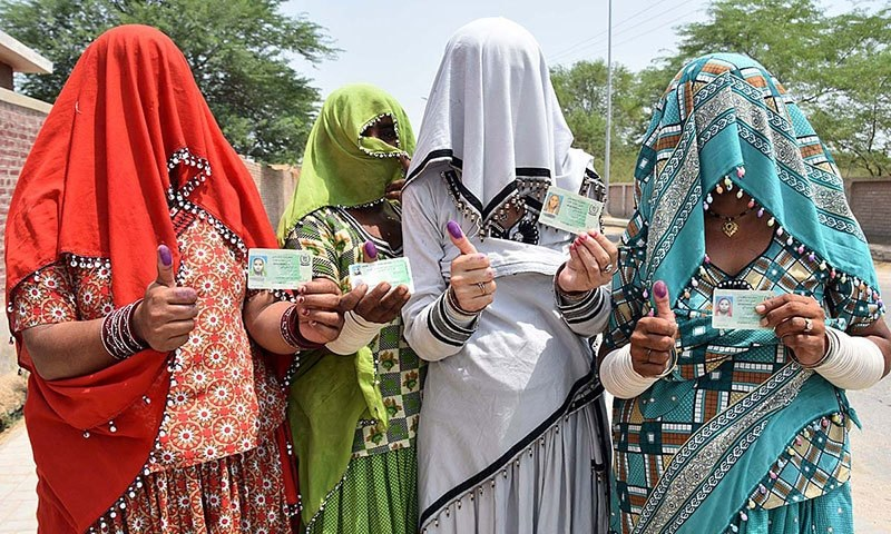 Four women showing their CNICs and marked thumbs after casting their votes in Ghotki by-polls on Tuesday, July 23, 2019. — APP